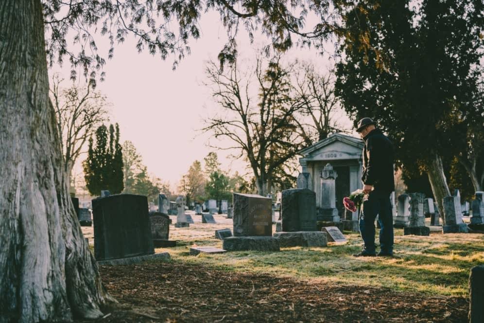 Veuf qui dépose des fleurs sur la tombe de feu son épouse pour la Toussaint